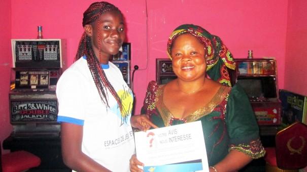 Un agent Lydia Ludic Togo remet un questionnaire à un gérant de bar partenaire